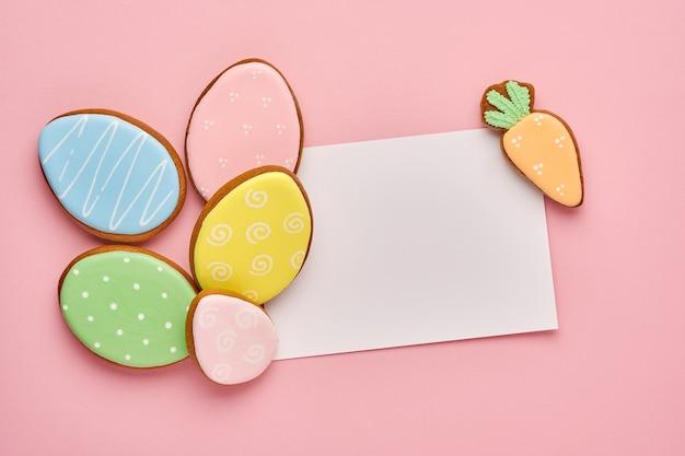 Поздравительная открытка пасхи с красочными кроликами, яйцами, цыплятами и пряниками моркови на розовом фоне с копией пространства. вид сверху.