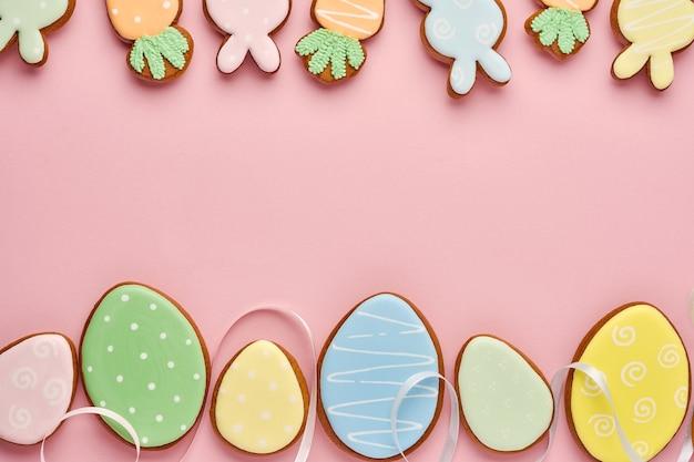 Поздравительная открытка пасхи с красочными кроликами, яйцами, цыплятами и пряниками моркови на розовом столе с космосом экземпляра. вид сверху