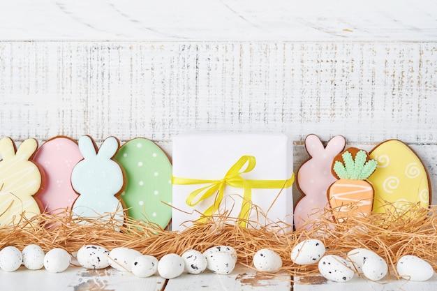 カラフルなウサギ、卵、鶏肉、ニンジンのジンジャーブレッドクッキーと白い木製の古い背景にコピースペースのあるイースターグリーティングカード。バナー。上面図。