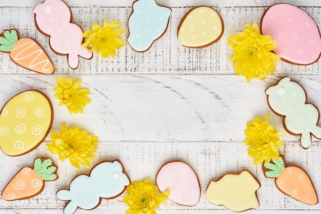 Поздравительная открытка пасхи с красочными кроликами, яйцами, цыплятами и пряниками моркови на белой деревянной старой предпосылке с космосом экземпляра. вид сверху.