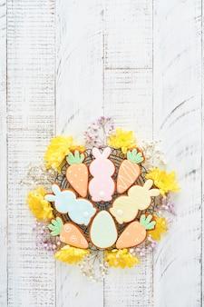 Пасхальная открытка с разноцветными кроликами, яйцами, цыплятами и пряниками с морковью