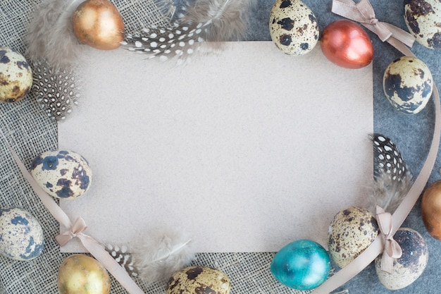 Easter greeting card with decor of eggs and feathers