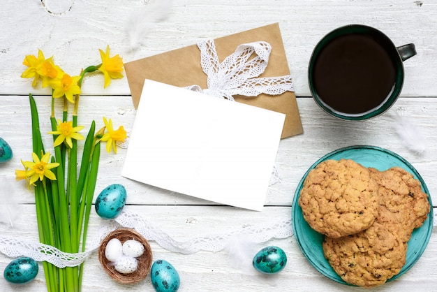 Easter greeting card with easter eggs, spring flowers, cup of coffee and cookies for breakfast