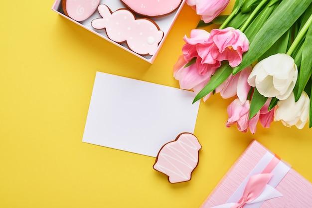 Пасхальная открытка с пасхальными пряничными яйцами в подарочной коробке и цветами тюльпана