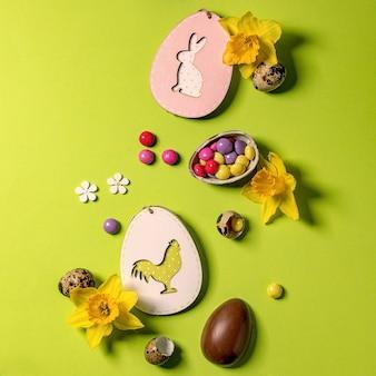 Пасхальная открытка с деревянными украшениями, шоколадными конфетами и яйцами