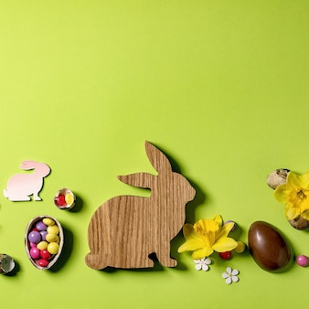 Easter greeting card with wooden decorations, chocolate sweets and eggs