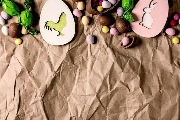 しわくちゃのクラフト紙の背景に木製のウサギと鶏の装飾、チョコレート菓子と卵とイースターグリーティングカード。フラットレイ、コピースペース。