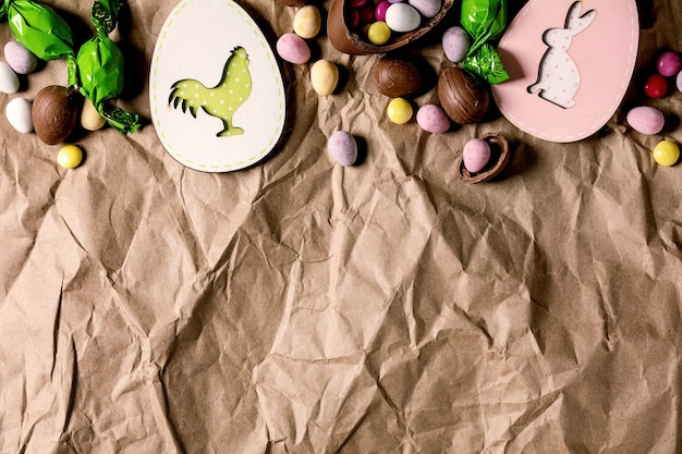 Easter greeting card with wooden rabbit and chicken decorations, chocolate sweets and eggs on crumpled craft paper background. flat lay, copy space.