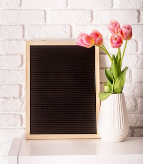 Easter hliday concept. vase with tulips and black felt letter board with words happy easter on white bricks background