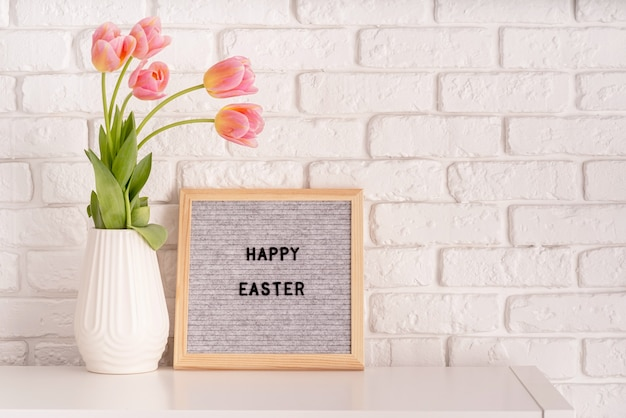 Easter hliday concept. vase with tulips and gray felt letter board with words happy easter on white bricks background