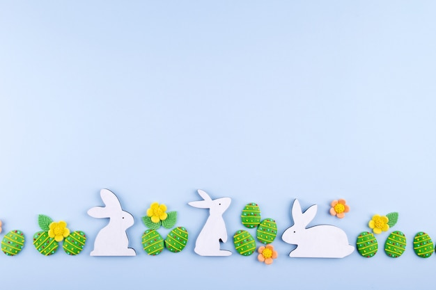 Easter holiday background. green sugar candy eggs, bunny on blue background. flat lay, top view