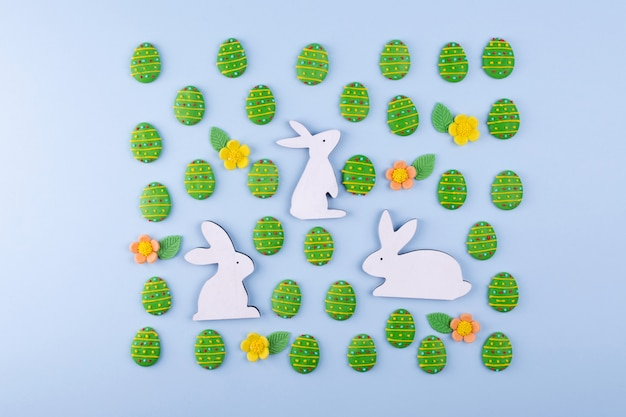 Easter holiday background. green sugar candy eggs, wooden bunny on blue background.
