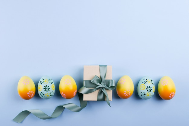 Easter holiday background  top view of colorful painted chicken eggs plased  in a row and present box with ribbon