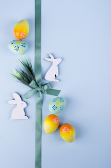 Easter holiday background with colorful painted chicken eggs decorative wooden bunny and flowers and ribbon. flat lay