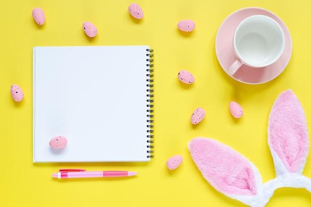 ノートとペン、コーヒーのカップ、ウサギの耳とイースターエッグとイースター休暇の背景。スペースの背景をコピーします。フラットレイ