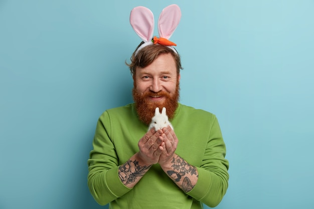 Easter holiday concept. bearded ginger man with tattooed arms holds tiny white fluffy rabbit, wears bunny ears, green jumper, has happy expression, isolated over blue wall. easter symbol