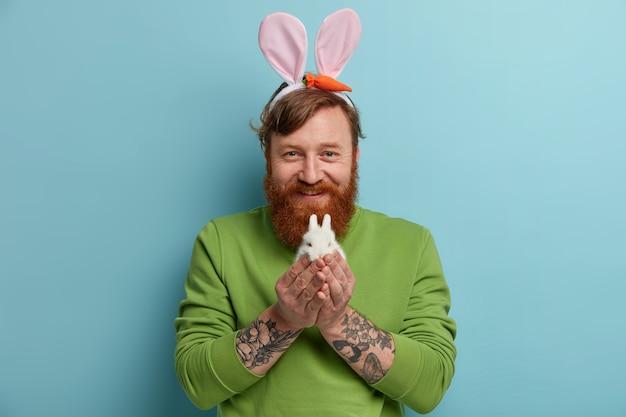 부활절 휴가 개념. 문신을 한 팔을 가진 수염 난 생강 남자는 작은 흰색 솜털 토끼를 잡고 토끼 귀, 녹색 점퍼를 착용하고 파란색 벽 위에 고립 된 행복한 표정을 가지고 있습니다. 부활절 상징