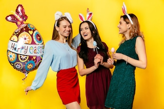 Easter. Holiday concept. Charming young women with balloon and painted eggs