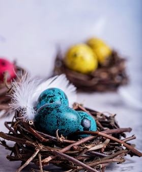 Easter holiday concept. colored easter quail eggs in a nest on gray marble background