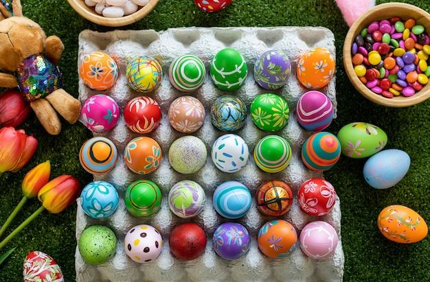 Концепция праздника пасхи, красочные пасхальные яйца в коробке для яиц, корзине пасхальные яйца, корзина для конфет, кукла кролика на фоне зеленой травы с космосом.