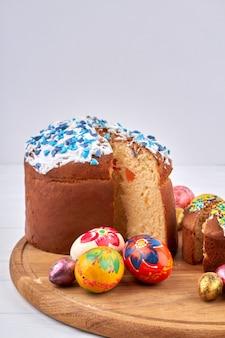 Концепция праздника пасхи. цветные яйца и домашние куличи на белом фоне.