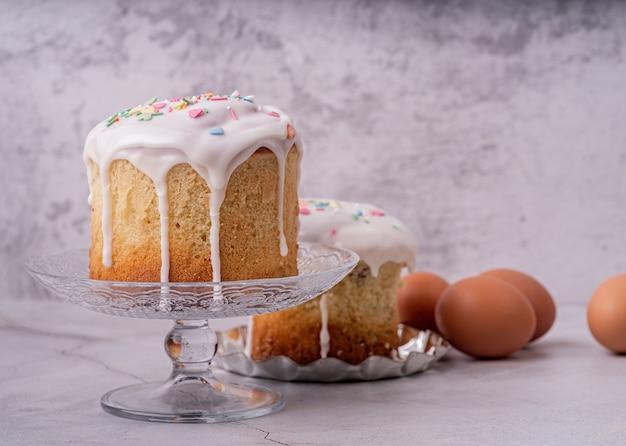 イースター休暇のコンセプト。コピースペースと白い大理石の背景正面図に卵とイースターケーキ