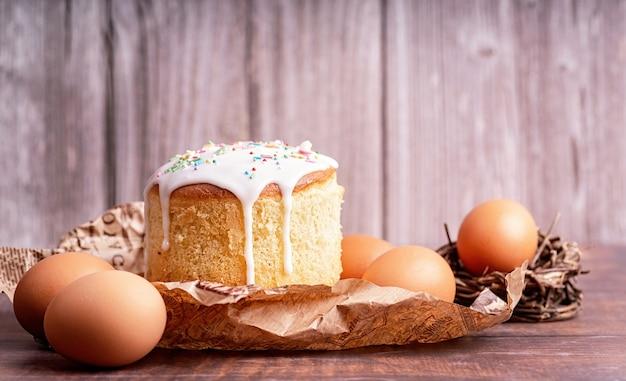 イースター休暇のコンセプト。木製の背景に卵とイースターケーキ