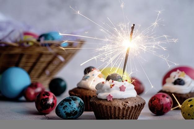 イースター休暇のコンセプト。色付きのウズラの卵で飾られた線香花火とイースターカップケーキ