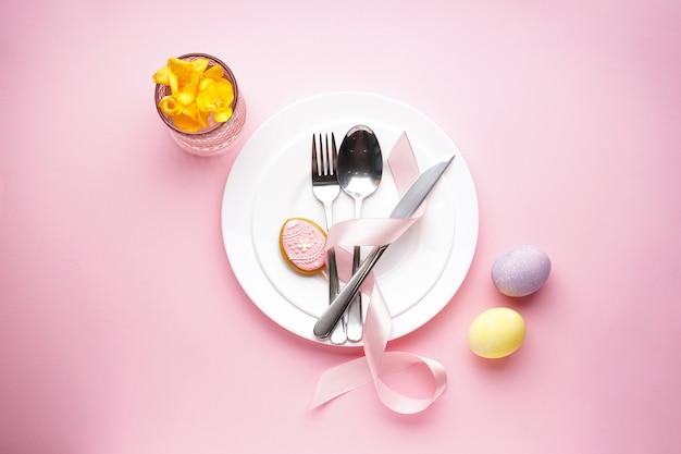 Концепция праздника пасхи. сервировка стола праздник пасхи на розовой поверхности. тарелки с красочными яйцами. вид сверху.