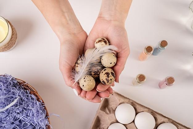 イースター休暇のコンセプト。ウズラの卵を持っている女性の手は着色のために赤く