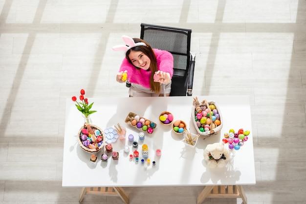 Концепция праздника пасхи, счастливая азиатская молодая женщина, держащая красочные пасхальные яйца на фоне белого деревянного стола в вид сверху