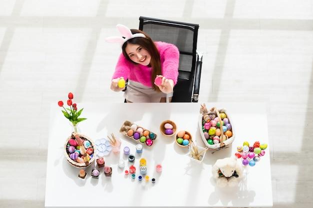 イースター休暇の概念、カラフルなイースターエッグのバスケットを持っているバニーの耳手を身に着けている幸せなアジアの若い女性