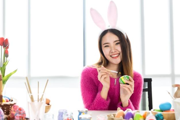 Концепция праздника пасхи, счастливая азиатская молодая женщина, носящая кроличьи уши, расписанные вручную яйца на пасху с красочными пасхальными яйцами на фоне белой комнаты