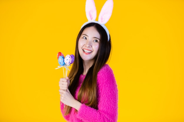 Easter holiday concept, happy smile asian young woman wearing bunny ears hand holding colorful easter eggs