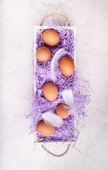 Концепция праздника пасхи. белая деревянная коробка с куриными яйцами на белом мраморном фоне вид сверху плоская планировка