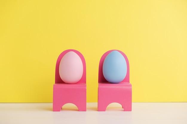 かわいい卵の生活とイースター休暇のコンセプト。さまざまな感情や感情。黄色の壁のピンクの椅子に座っている素敵なカップルの卵。