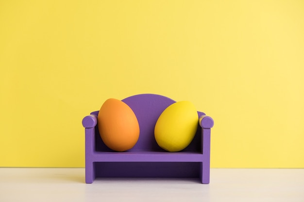Easter holiday concept with cute eggs life. different emotions and feelings. lovely couple eggs sitting on the sofa.