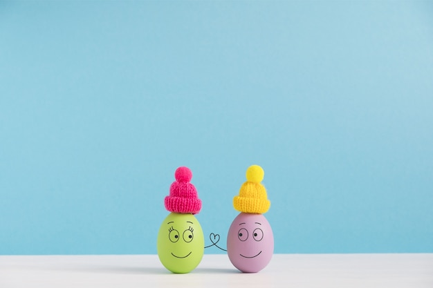Easter holiday concept with cute eggs with funny faces. different emotions and feelings. lovely couple in hats holding hands.