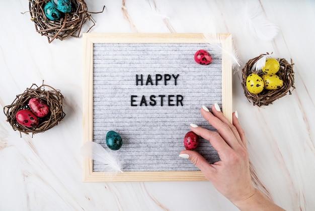 イースター休暇のコンセプト。ハッピーイースターの上面図フラットレイという言葉でフェルトのレターボードに色のウズラの卵を置く女性の手