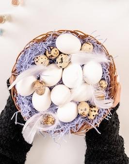 イースター休暇のコンセプト。卵と羽の上面図で大きなバスケットを保持している女性の手