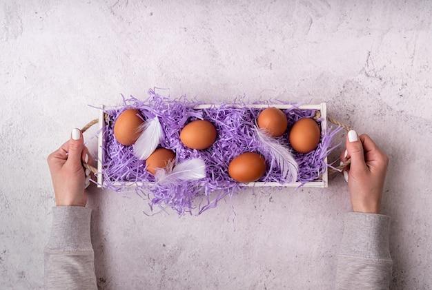 부활절 휴가 개념. 흰색 대리석 배경 평면도 평면 누워에 닭고기 달걀과 흰색 나무 상자를 들고 여자 손