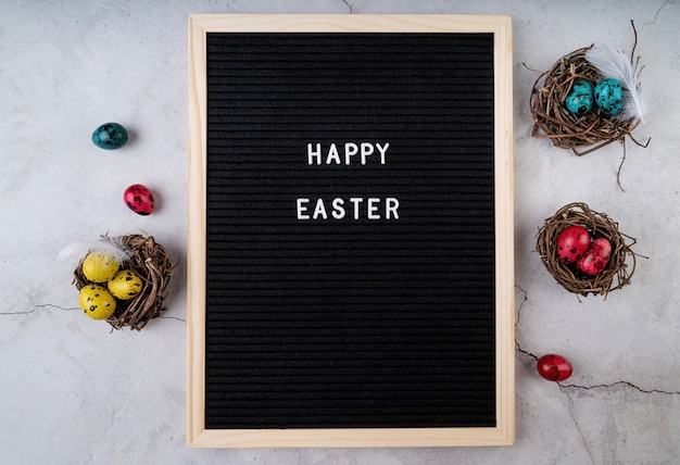 Easter holiday concept. the words happy easter on black felt letter board decorated with quail eggs and feathers on marble background