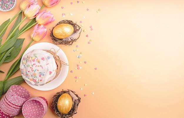 Праздник пасхи креативный фон с куличом, яйцами в гнездах, тюльпанами и украшениями, вид сверху, плоская кладка с копией пространства