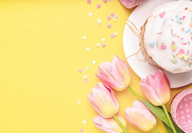 Пасхальный праздник творческий фон с пасхальным куличом, тюльпанами и украшениями, вид сверху, плоская планировка с копией пространства