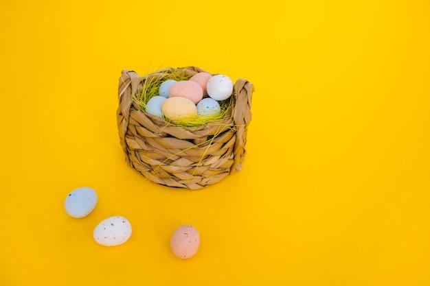 黄色の背景にイースターの休日の装飾カラフルなイースターはバスケットにまだらの卵を描いた