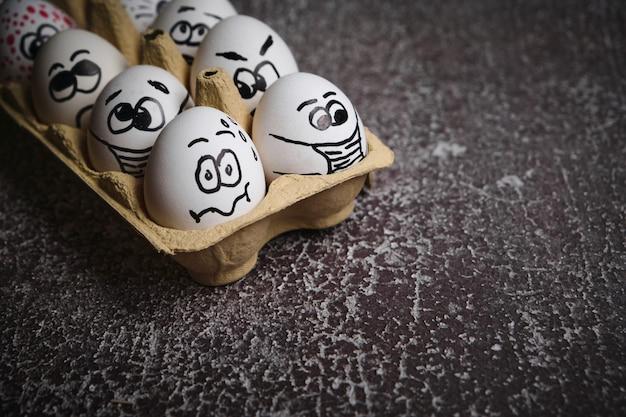 マスクのイースター休暇の卵。コロナウイルスの流行中のイースター休暇中に医療マスクを身に着けている描かれた変な顔と白い卵のトレイ