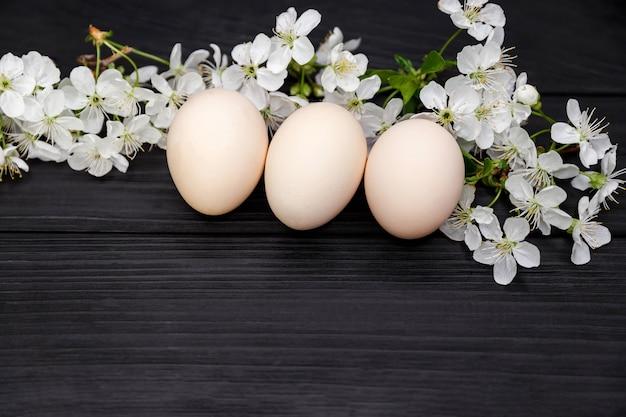 イースターホリデー。花の枝で自然な卵。桜の花とスタイリッシュな無着色のイースターエッグは、柔らかな光の中で暗い木製の背景に枝分かれします。テキスト、上面図、フラットレイ用のコピースペース