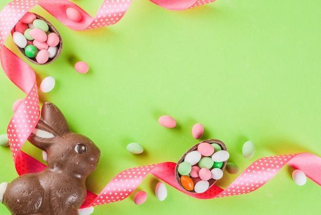 Easter holiday greeting card background, with chocolate easter bunny, candy eggs, quail eggs and festive ribbon