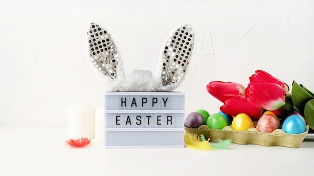 イースターホリデー。ウサギの耳と白い背景の上のイースターの装飾とハッピーイースターライトボックス