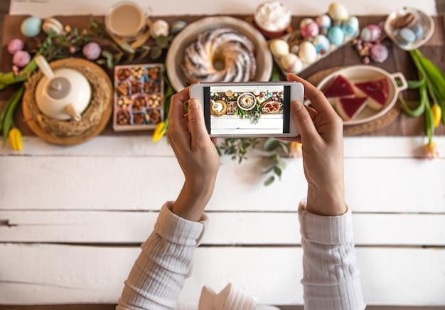 イースターホリデー。お祝いのイースターランチや朝食に、携帯電話からの写真。美しく保存されたテーブル。家族の価値観とイースター休暇。上面図